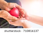 Small photo of Philanthropy health care concept. Caregiver with senior people hands with heart in palm in hospice center with copyspace. Public Service Recognition Week