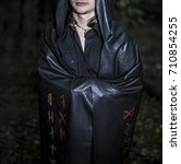 Small photo of Portrait of a brutal man in a black robe. satanist wear dark shroud with bloody runes against night forest.