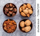 Small photo of Whole almonds,whole walnuts ,whole hazelnut and pecan nuts in wooden bowl setup with stone background. Selective focus depth of field.