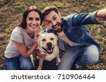 Stock photo beautiful romantic couple is having fun with their dog labrador retriever outdoors sitting on a 710906464