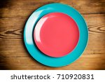 Two Colored Plates On A Wooden...