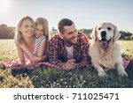 Stock photo beautiful happy family is having fun with golden retriever outdoors mother father and daughter 711025471