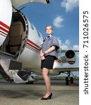 air hostess beside private jet. | Shutterstock . vector #711026575