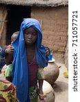 Small photo of FARAFENNI, GAMBIA - JANUARY, 11, 2017: Unidentified Gambian girl with baby.