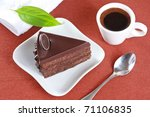 Closeup of chocolate cake on a white plate and a cup of coffee on a brown background - stock photo