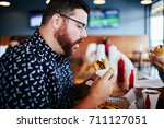 man about to eat a burger hungry | Shutterstock . vector #711127051