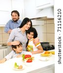 Happy family of four members in kitchen - stock photo
