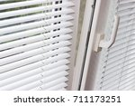 Small photo of Fragment of the modern tilt and turn plastic window tilted inwards at the top with control handle and white Venetian blinds
