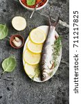 Small photo of A river white fish of the Cyprinidae family on a gray stone background with herbs, lemons and salt before cooking. Top View