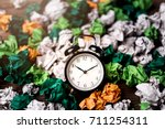 Small photo of Alarm clock in a wastepaper concept for a time waste of time with cork board texture background