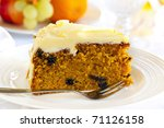 Carrot cake with cake fork.  Healthy fruit behind. - stock photo