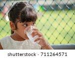 thai girl is drinking water... | Shutterstock . vector #711264571