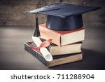 graduation hat and diploma with ... | Shutterstock . vector #711288904