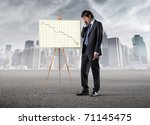 Sad businessman standing beside a graphic with negative trend - stock photo