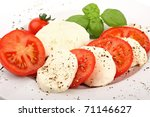 mozzarella and tomato slices with pepper and basilicas. - stock photo