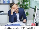 businessman dozing at his desk | Shutterstock . vector #711562825