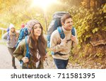 Small photo of adventure, travel, tourism, hike and people concept - group of smiling friends walking with backpacks in autumn forest