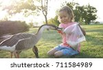 Small photo of Cute little girl feeding wild goose from palm at green meadow but goose attack and plucked her. Child with dander geese