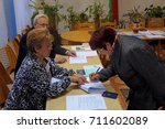Small photo of Belarus, Bobruisk district, Gorbatsevichi village, October 8, 2015: A woman voter puts his signature on the list, and members of the precinct commission show where.