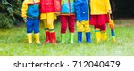 kids in rain boots. group of... | Shutterstock . vector #712040479