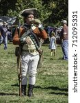 Small photo of WHEATON, ILLINOIS/USA - SEPTEMBER 9, 2017: A British infantryman drinks from a canteen before a tactical military demonstration at a reenactment of the American Revolutionary War (1775-1783).