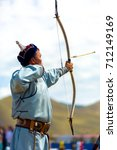 Small photo of Ulaanbaatar, Mongolia - June 11, 2007: An arrow flying mid-air after launched by a male archer in traditional garb at the Naadam Festival archery competition