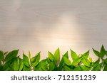 green leaf frame on wood... | Shutterstock . vector #712151239