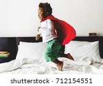 Small photo of African descent kid jumping on the bed with robe