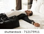 exhausted young businessman... | Shutterstock . vector #712175911