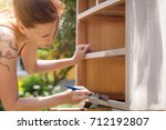 woman is painting an old... | Shutterstock . vector #712192807
