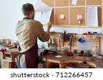portrait of man in apron... | Shutterstock . vector #712266457