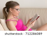 Small photo of Young woman enjoying fiction book on sofa at living room, attractive hipster girl in glasses for reading immersed in new bestseller or classic novel, student studying course literature before exam