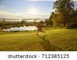 happy boy running through the... | Shutterstock . vector #712385125
