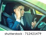 Small photo of Driver man with a mobile phone in hands makes an accident. Fright, inconsiderate and dangerous driving. The traffic violation.