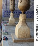 Small photo of Base of stone of wood graven columns of the building Tosh-Hovli with after all a blue decorated ceramics wall in the city museum of Khiva in Uzbekistan. August 2017