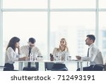 the four business people sit at ... | Shutterstock . vector #712493191