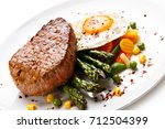 grilled steak with asparagus... | Shutterstock . vector #712504399