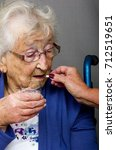 Small photo of Senior Citizen taking Pill A senior citizen, in a wheelchair, being given her medication by a carer.