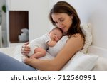 young mother lying in bed with... | Shutterstock . vector #712560991