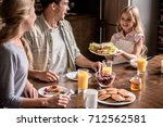 happy family having breakfast... | Shutterstock . vector #712562581