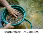 Small photo of Gold panning and gem mining. Prospecting tool of classifier used to sift and sort material. Classify mineral rich soil, dirt, pebbles and stones. Prepare soil to pan. Fun, adventure and recreation.