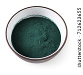 Small photo of Spirulina algae powder in a clay cup isolated on white background. Top view. Super food concept