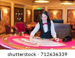 cute lady casino dealer at... | Shutterstock . vector #712636339