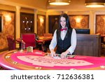cute lady casino dealer at... | Shutterstock . vector #712636381