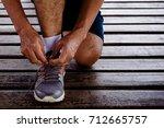 young runner man tying his... | Shutterstock . vector #712665757