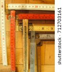 Small photo of A variety of old antique tools: Folding rulers both metric and inches on a wooden surface represent measurement, accuracy, and preciseness, vertical format.