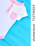 Small photo of Cute cotton romper for baby-girl. White organic bodysuit for newborn on blue wooden background, top view. Infant kid summer outfit.