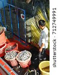 Small photo of Prachuap Khiri Khan, THAILAND - JULY 16 : 2011. Labour fishermen at the fish port in Hua Hin Beach.