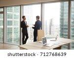 two businessmen having coffee... | Shutterstock . vector #712768639