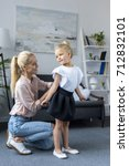 happy young mother dressing... | Shutterstock . vector #712832101